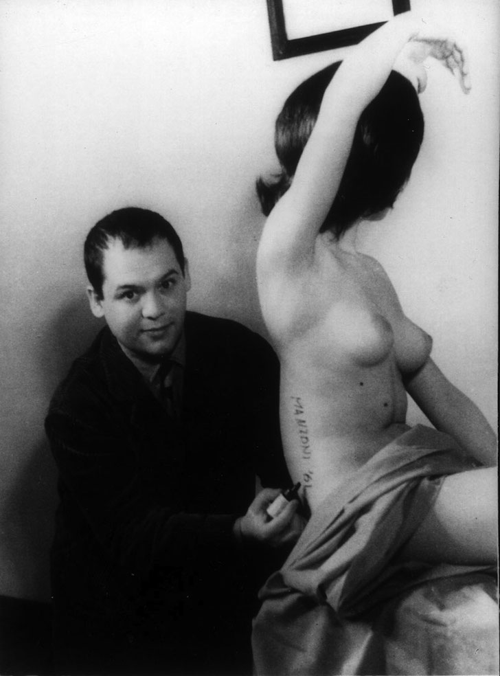FOTO MANZONI SCULTURA VIVENTE Piero Manzoni firma una modella trasformandola in Scultura vivente, durante le riprese per il filmgiornale S.E.D.I., Milano 1961