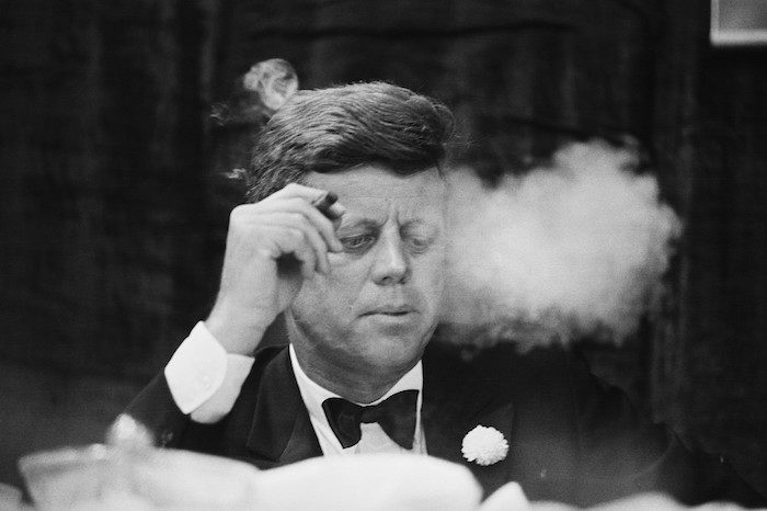 19 Oct 1963 --- President John F. Kennedy smokes a cigar during a Democratic fundraising dinner at the Commonwealth Armory at Boston University. --- Image by © Bettmann/CORBIS